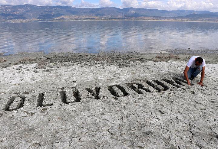 Side-specific enstalasyon (mekana özgü yerleştirme) ve bir performans çıktısı olarak nitelendirilebilecek sanat eserini, Burdur Gölü kumsalında yapan Ali İbrahim Öcal, gölün kuruyan alanında sahile elleriyle ölüyorum mesajı yazdı.