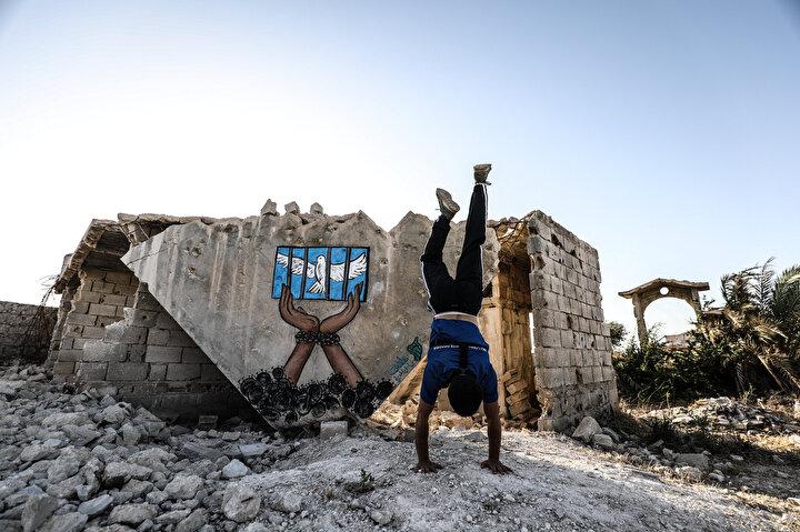Parkur sporu tutkunu gençler, Esed rejiminin yaptığı saldırılara dikkati çekmek için tehlikeye aldırmadan enkaz arasında spor faaliyetlerine devam ediyor.