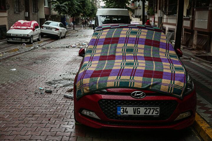 Sultangazide biranda etkili olan dolu ve sağanak yağıştan sonra, vatandaşlar koruma amaçlı araçlarının üzerine halı, kilim, battaniye serdi.