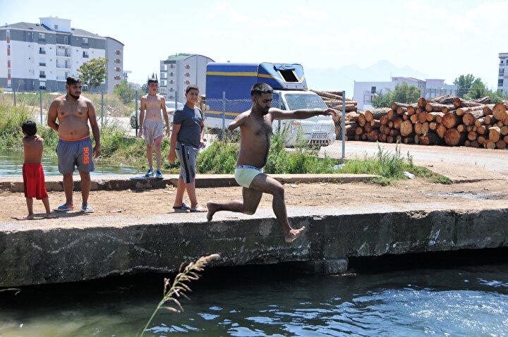 Hava sıcaklığının 34, hissedilenin ise 38 derece olduğu Antalyada yetişkinler ve çocuklar, serinlemek için denizin yanı sıra, su kanallarını tercih ediyor.
