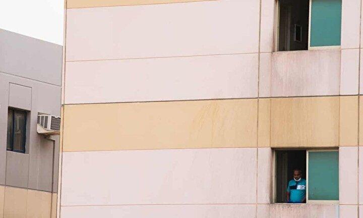Hasan ve 98 iş arkadaşı, eski işverenlerine ait olan şehrin bir ucundaki çalışma kampında hayatlarını idame ettirmeye çalışıyor. Sarı beton duvarlara sahip üç katlı U şeklindeki binada, metal ranzalarla dolu düzinelerce eski püskü yatakhane bulunuyor. Bu kadar sıkışık yaşamda sosyal mesafe zaten  mümkün değil. Bina çift  çitle çevrilmiş ve güvenlik görevlileri tarafından  korunuyor. Altı ay önce önce büyük etkinliklerin düzenlendiği mutfakta ise şu anda pişirilecek hiçbir şey yok.