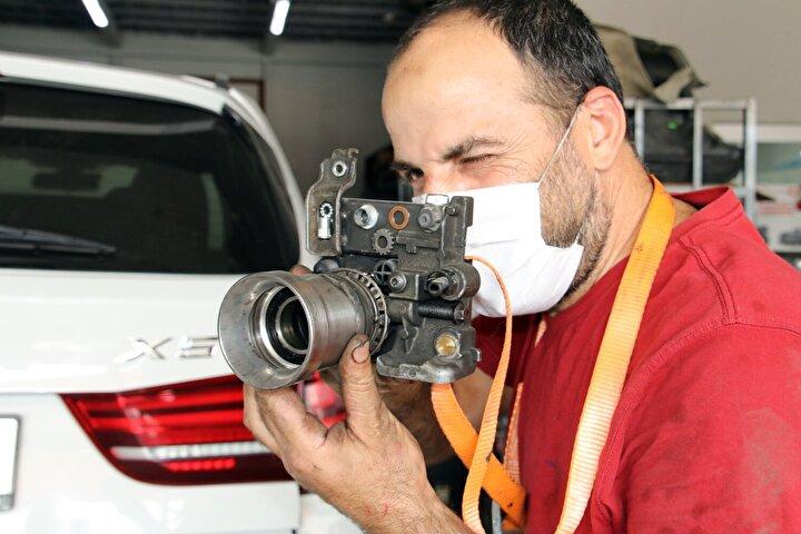 Murat Çetin eserlerini iş yerinde sergilerken, araçlarını tamir için getirenler eserleri ilgiyle inceliyor.