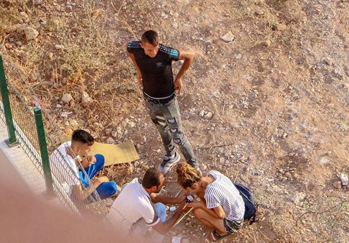 Uyuşturucu kullanmaya devam eden grup, yolda yürüyenlere aldırış dahi etmedi. Bir süre sonra araziye bastonla yürüyen engelli bir kişi geldi. Taşların üzerine oturan kişi, bir elindeki aynayla boynuna bakarak yer arayıp, diğer elindeki şırıngadaki uyuşturucuyu enjekte etti.