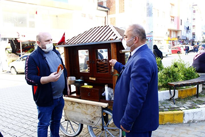 İlçede kimileri, tatlı satın aldığı Öztürk'le anı fotoğrafı çektiriyor.