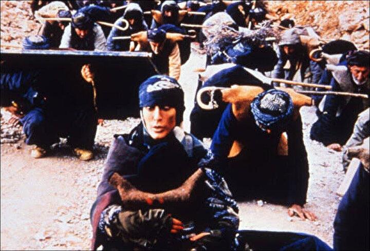 Öğretmenler, bir savaş sonrası yıkımının yaşandığı bir toplumda, sırtlarına yükledikleri kara tahtalarla eğitim için seyahat etmektedirler.