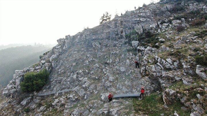 Belediyenin ihale ettiği işi alan firma çalışanı 10 kişilik dağcı grubu 250 kilo ağırlığında 50 metre genişlikte 4 metre boyunda çelik tel ruloları uçurumdan aşağıya iple sarkıtıp istasyonlar kurarak kayalara sarıyor.