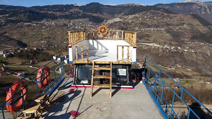 15 metre uzunluğunda, 4.60 metre genişliğindeki tekneyi denizden Akçaabat ilçesine getiren Zafer tekneyi vinç yardımıyla tıra yükledi. Tek şeritli, rampalı ve virajlı yollardan geçilerek ilçedeki 661 rakımlı Yenimahalle'ye getirilen tekne, daha önceden yapılmış beton yapının üzerine yerleştirildi. 'Saback rüzgarı' adı verilen tekne ilçeye hakim bir noktaya konumlandırılırken, yerli ve yabancı turistlerin uğrak yerlerinden biri olan Haçkalı Baba Yaylası'na giden yol güzergahındaki tekne görenlerin ilgisini çekiyor.