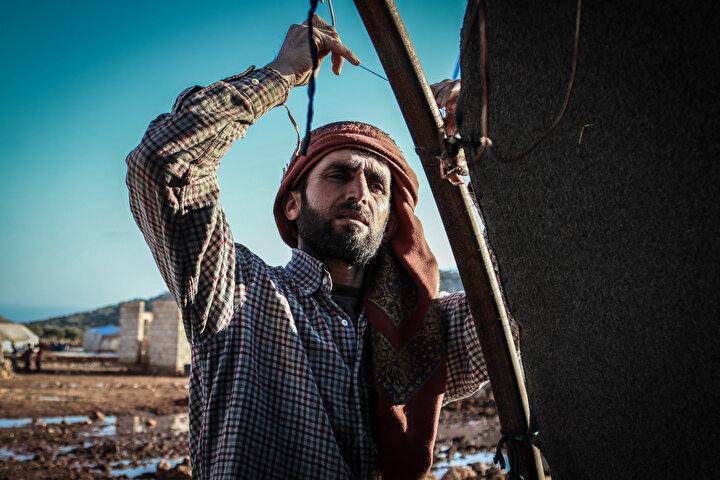 Serakib ilçesinden göç eden 8 çocuk annesi Ayşe Um Ahmet, battaniyeleriler ve minderlerden yaptıkları çadırlarda yaşadıklarını, geceleri çok üşüdüklerini söyledi.