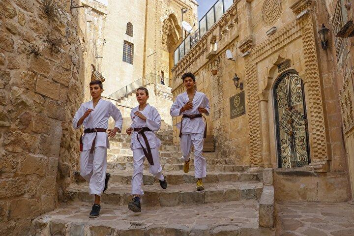 Koronavirüs tedbirleri kapsamında, 20 yaş altındakiler için getirilen 13.00- 16.00 saatleri dışındaki sokağa çıkma kısıtlamasında Mardindeki genç karateciler Enes Ömer Yıldızoğlu (14), Hüseyin Çaça (13) ve Abdullah Can (13), gelecek aylarda yapılacak milli takım seçmelerine hazırlanıyor. Genç karateciler, bu süreçte çalışmalarını hem evlerinde hem de kısıtlamadan muaf oldukları saatlerde, antrenörleri Murat Kaya eşliğinde kentin tarihi ve dar sokaklarında antrenman yaparak sürdürüyor. Uzun süre evde kalmaları nedeniyle çok basamaklı merdivenlerde koşu yapan karateciler, hız, kuvvet ve dayanıklılığa yönelik antrenmanlarla milli takıma girmek için ter döküyor.