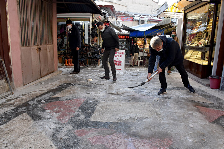 Saraçlar Caddesinde esnaf, iş yerlerinin önünü kaplayan buzları küreklerle kırarak, temizledi.
