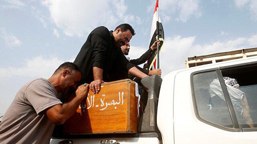 Iraklı bir adam Basra'da gerçekleşen bir cenaze töreni sırasında hükümet karşıtı protestolarda öldürülen bir göstericinin tabutunda yas tutuyor.