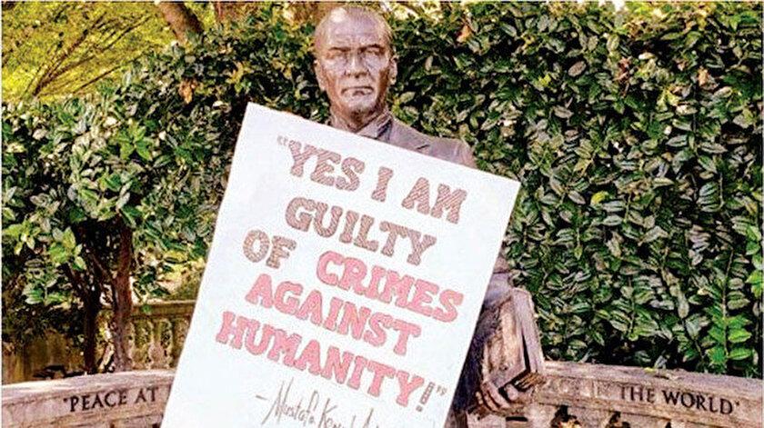 """Heykelin üzerine İngilizce """"Evet, insanlığa karşı işlenen suçlardan suçluyum"""" yazısı asıldı."""