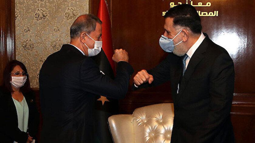 Bakan Akar ve Libya Başbakanı Serrac'ın koronavirüs nedeniyle yaptığı selamlaşma.