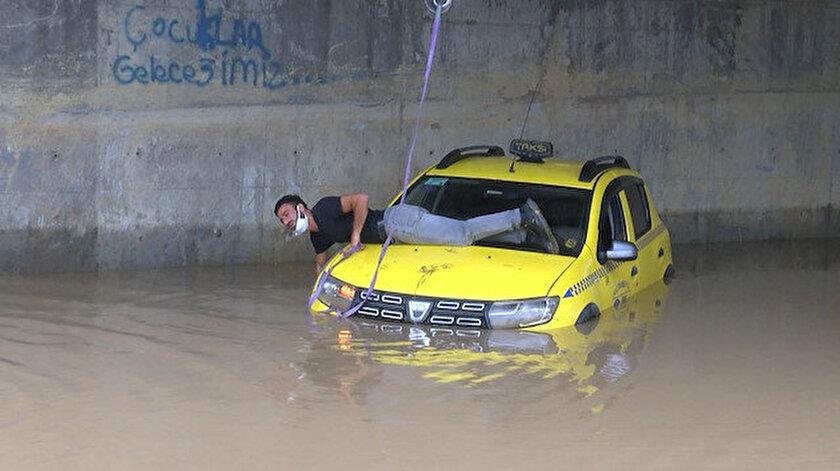 Alt geçidin altında mahsur kalan taksici, aracının üstüne çıkıp kurtarılmayı bekledi.
