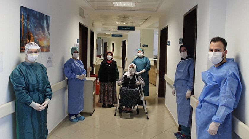 Yaşlı kadın sağlık çalışanlarının eşliğinde taburcu edildi.