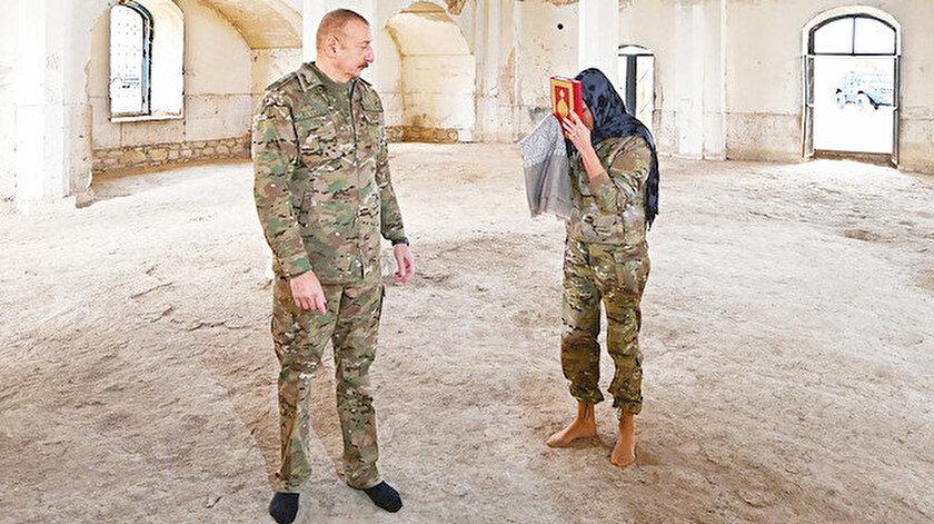 Aliyev çifti, zemininde halı bulunmayan camiye ayakkabılarını çıkarıp girdi.