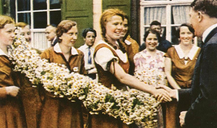 Mağlubiyet anında nezaket tanımam! Bund Deutscher Mädel (Alman Kızları Birliği) Hitler'i çiçekler eşliğinde, samimi bir şekilde karşılıyor. Hitler'in de onlardan aşağı kalır yanı yok. Ne var ki, mağlubiyet kapıdayken çocuk yaştaki Alman kızları dahi silah altına almaktan çekinmeyecekti.