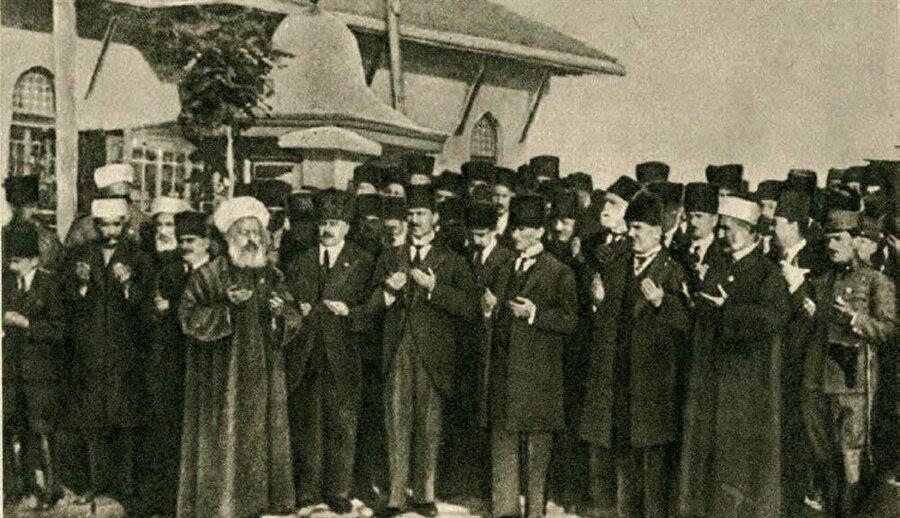 Meclis'in önünde bir dua merasimi. Mustafa Kemal, özellikle BMM'nin açıldığı dönemde mevcut şartları göz önünde tutmak suretiyle dinî söylem yoğunluklu bir üslûp tercih etmişti. Sağındaki Rauf Orbay, solundaki ise Ali Fuat Cebesoy.