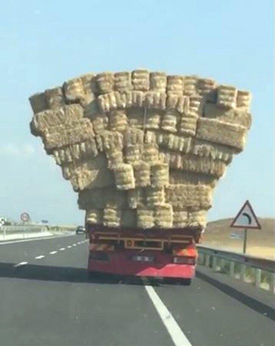 Üzeri aşırı saman balyaları yüklü kamyonun tehlikeli yolculuğu görenleri hayrete düşürdü.