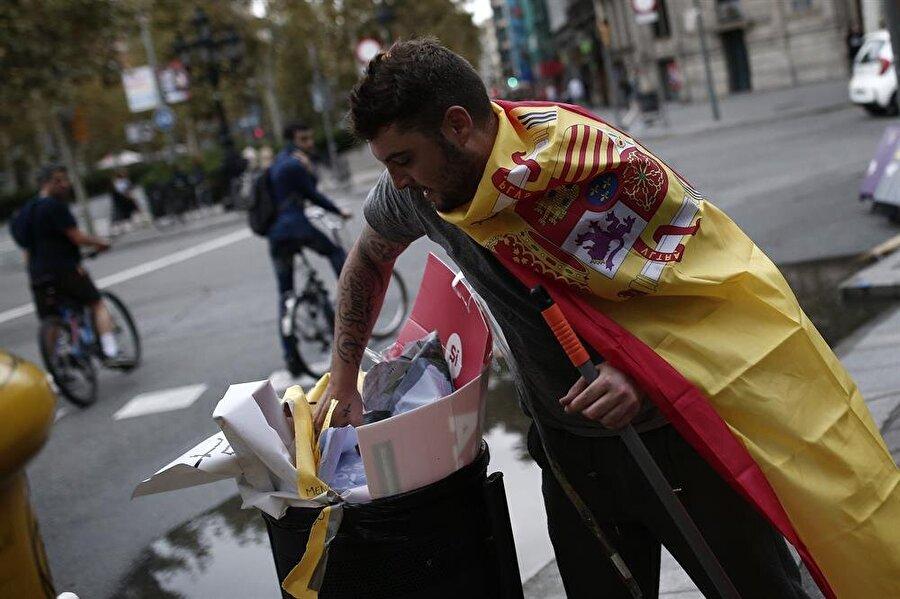 Bağımsızlık karşıtı İspanyollar, ayrılıkçıların afişlerini çıkarıp çöpe attı.
