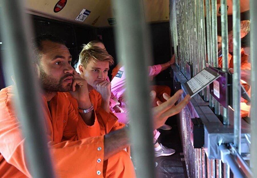 Tüm oyunculara hapishane elbiseleri giydirildi ve elleri kelepçeli halde ormana bırakıldı.