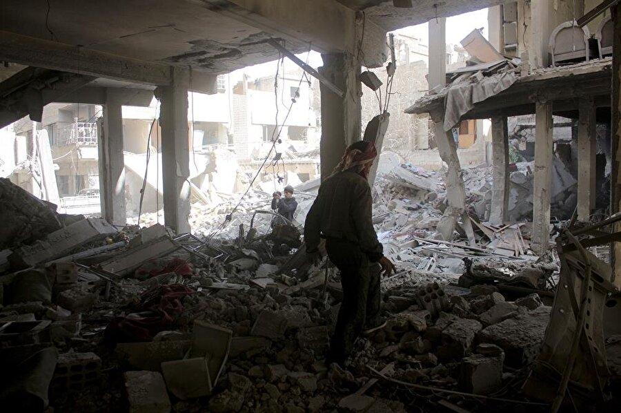 Görüntülerde insanlardan çok ağır hasar almış apartmanlar, tahrip olmuş tozlu yollar göze çarpıyor.