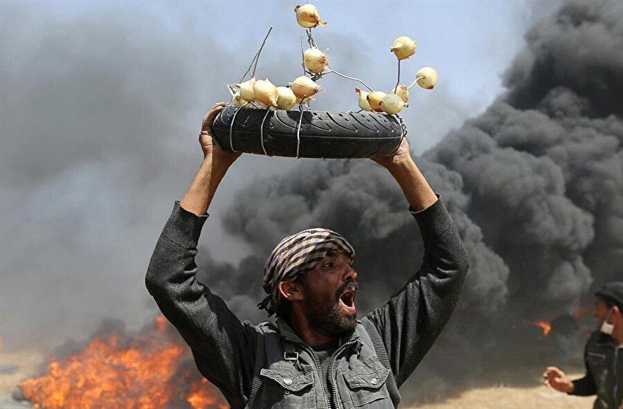 "Bir Filistinlinin taşıdığı ""el yapımı göz yaşartıcı silah"". (Ibraheem Abu Mustafa / Reuters)"