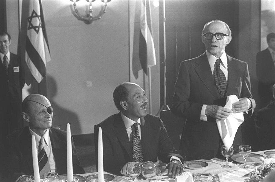 Mısır Cumhurbaşkanı Enver Sedat (Ortada), İsrail'de şerefine verilen yemekte, İsrail Başbakanı Menachem Begin (Sağda) ve İsrail Savunma Bakanı Moshe Dayan (Solda) ile birlikte.