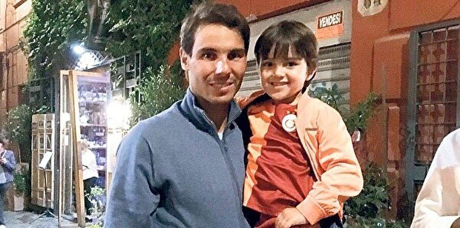 Ünlü tenisçi Rafael Nadal, Galatasaray'ın Göztepe maçını izledi ve çevresinde bulunan sarı-kırmızılılarla şampiyonluğu kutladı.nnSkorer'de yer alan habere göre İtalya'nın Roma kentinde bir mekanda, menajer Bayram Tutumlu ile birlikte karşılaşmayı izleyen Nadal, Tutumlu'nun oğlu Masoud'un coşkusuna ortak oldu.nnÜnlü raketin, sarı-kırmızılı renklere büyük sempati duyduğunu ve Galatasaray taraftarı olduğunu söyleyerek mutlaka bir maç izlemek için İstanbul'a geleceğini dile getirdiği aktarıldı.