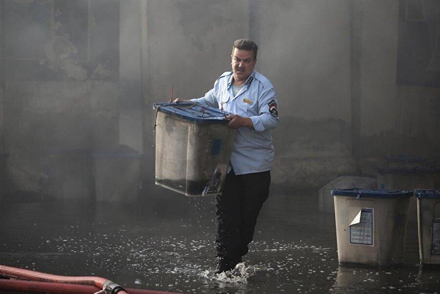 Görevliler, sandıkların küle dönmesini önlemek için yoğun çaba sarf etti. (Reuters)