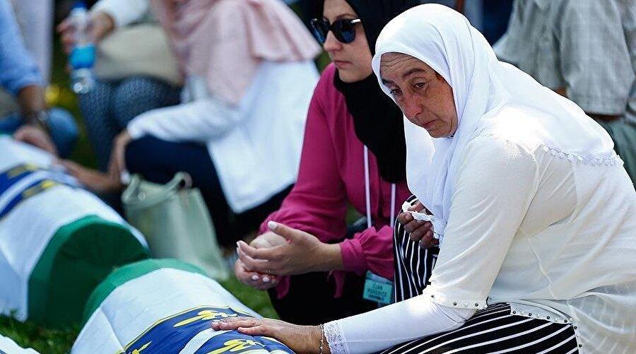 Kimlik tespiti yapılan kurbanlar aileleri tarafından toprağa veriliyor. (Fotoğraf: Anadolu Ajansı)
