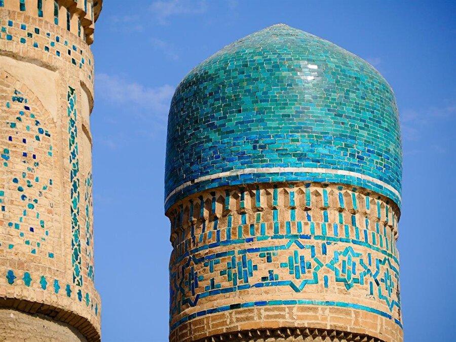 Yapının minareleri, turkuaz taşlarla örtülmüş zirveleriyle dikkat çekiyor.