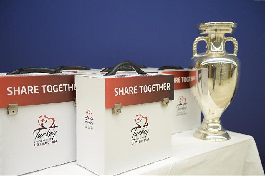 Şampiyonun ellerinde havaya yükselecek kupanın imitasyonu ve Türkiye'nin kiti.
