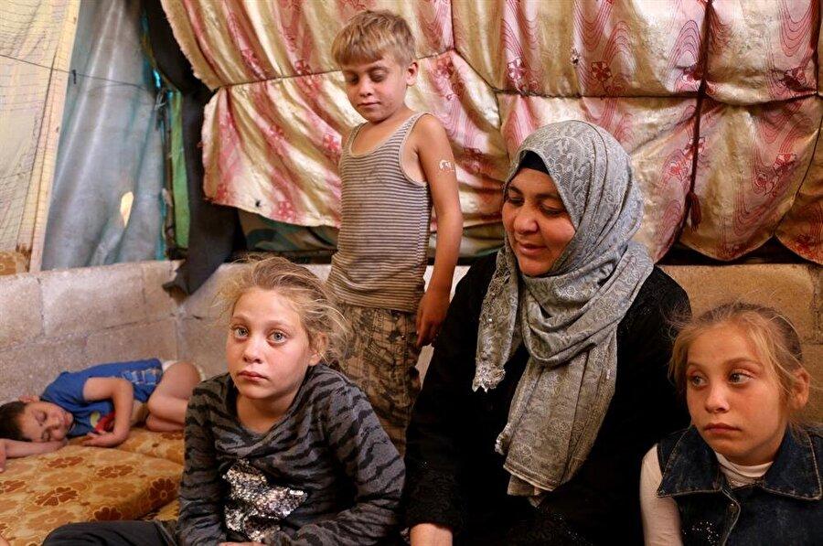 Um Ahmet ve ailesi, derme çatma bir çadırda, oldukça zor koşullarda yaşıyorlar. (Muhammed Abdullah / AA)
