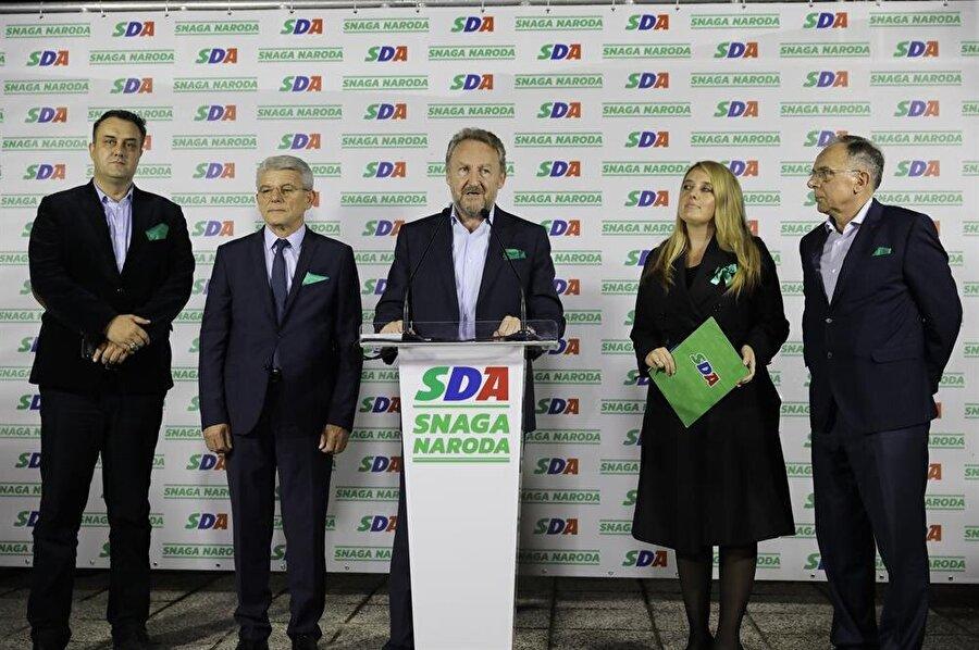 Devlet Başkanlığı Konseyi Başkanı Bakir İzetbegovic'in (ortada) başkanı olduğu SDA partisinin adayı, konseyde Boşnaklar için ayrılan sandalyeye oturmaya hazırlanıyor.