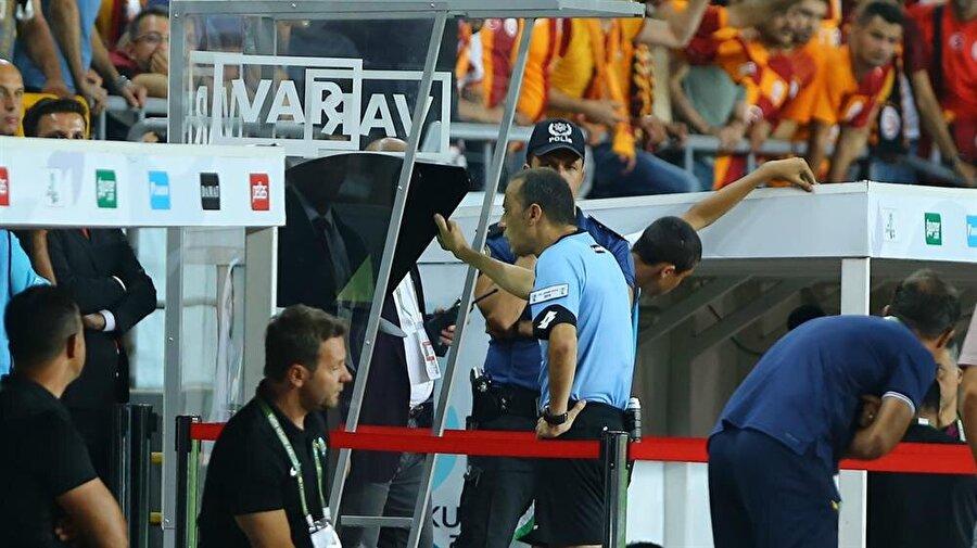 FIFA kokartlı hakemimiz Cüneyt Çakır, Galatasaray maçında VAR'a başvuruyor ve ilgili görüntüleri tekrar izliyor.