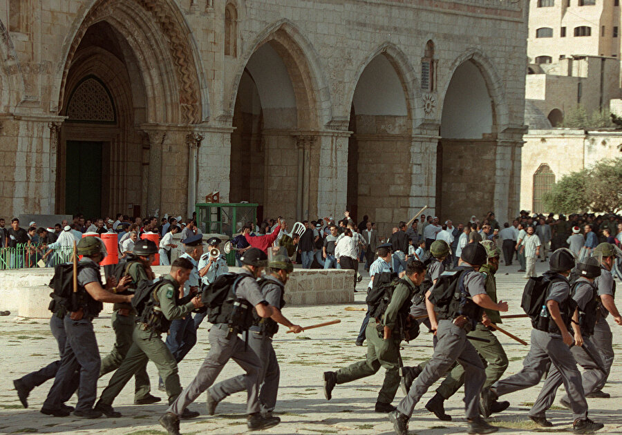 Filistinli gençlerle İsrail askerleri arasında Aksa avlusunda yaşanan çatışmalardan bir kare.