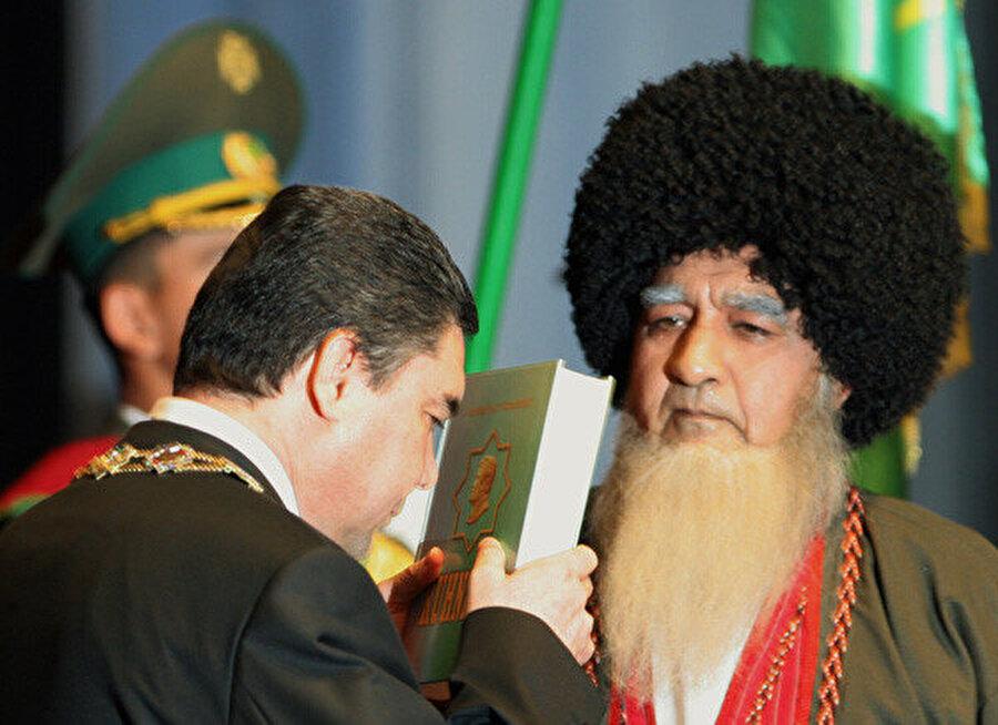 """Saparmurat Niyazov'un ölümü sonrası iktidara gelen Gurbanguli Berdimuhammedov yemin töreninde Kur'an'la birlikte Niyazov'un yazdığı """"Ruhname"""" kitabına da yemin ederek başına koydu. (14 Şubat 2007)"""