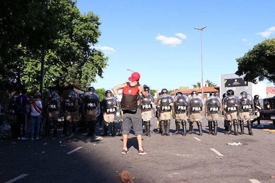 River Plate taraftarı polis şeridinin önünde tezahüratlarda bulunuyor.