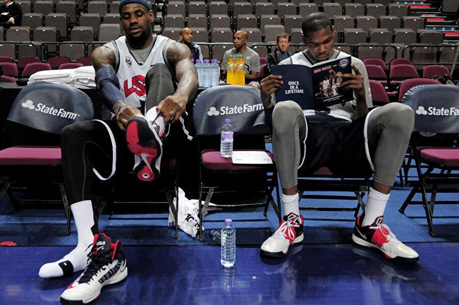 LeBron James ve Kevin Duran All-Star formasıyla benchte okuma yapıyor.