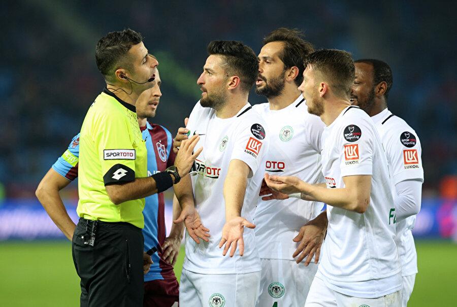 Atiker Konyaspor forması giyen oyuncular hakem Mete Kalkavan'a tepki gösteriyor.