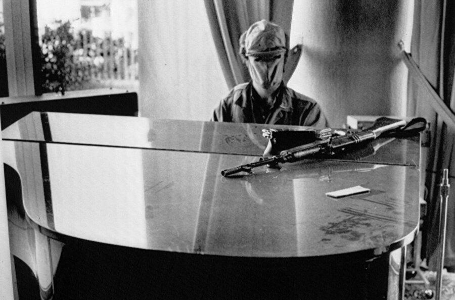 Holiday Inn'i ele geçiren Falanjist Hıristiyan grubundan bir asker, tüm o mermilerin arasında ayakta kalmayı başarmış bir piyanoyu çalmaya çalışıyor.