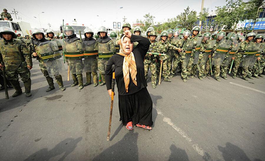 Çinli askerlerin önünde direnen bir Uygur Türkü.