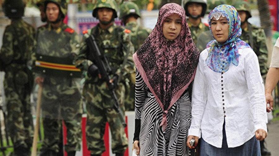 Çinli askerlerin gölgesinde iki Uygur Türkü.