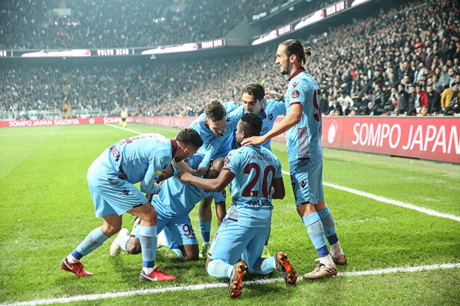 Trabzonspor forması giyen oyuncular köşe gönderinde golün sevincini paylaşıyor.