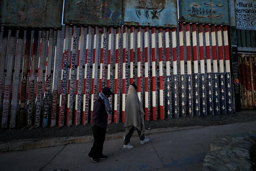 Amerikan bayrağının resmedildiği bir duvarın yanında iki ABD'li.