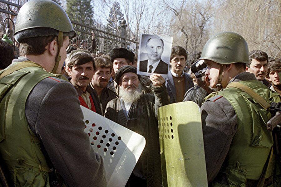 Tacik iç savaşı sırasında çekilmiş bir kare: Elinde Mihail Gorbaçov'un posterini tutan bir Tacik ve askerler karşı karşıya...