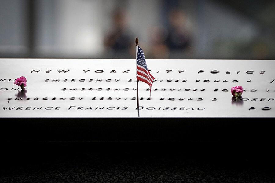 Saldırıda hayatlarını kaybedenler için yapılan anıta, ABD bayrağı ve çiçek bıraktılar.