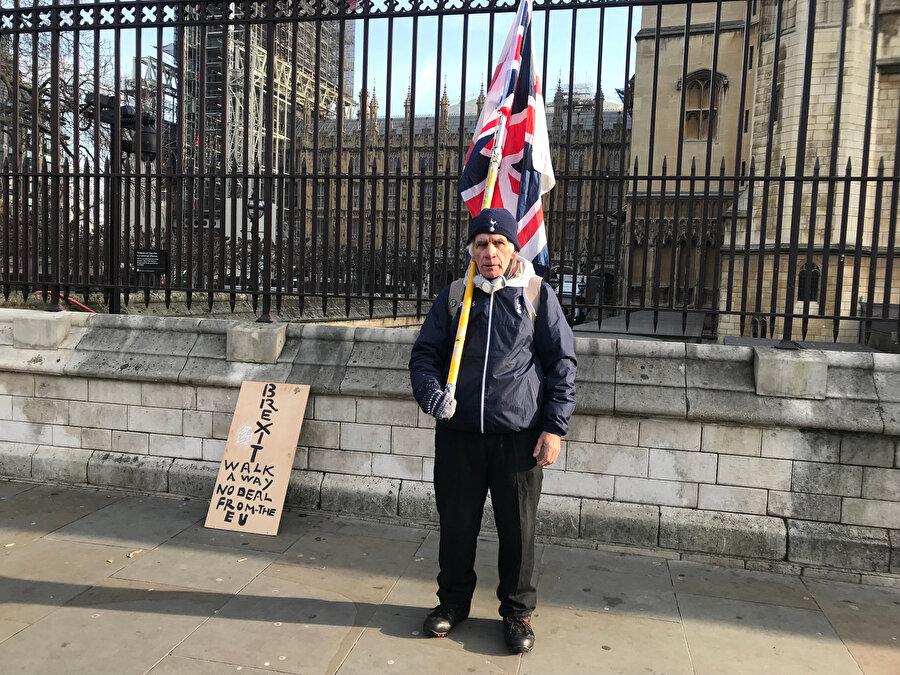 İngiltere bayrağıyla parlamento binasının kapısında nöbet tutan Thomas.