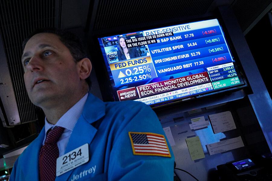 New York Borsası'nda (NYSE) faiz oranlarının yükseldiğini gösteren TV ekranı ve bir yatırımcı.